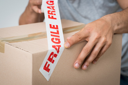 Foto de Close up Of A Man Packing Cardboard Box With tape - Imagen libre de derechos