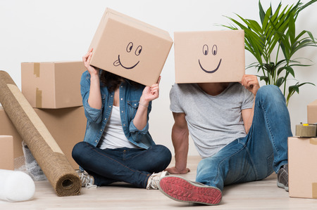 Photo pour Couple With Cardboard Boxes On Their Heads With Smiley Face Sitting On Floor After The Moving House - image libre de droit