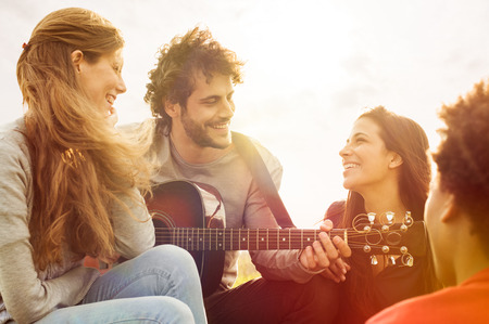 Photo pour Happy group of friends enjoying the summer outdoor playing guitar and singing together - image libre de droit