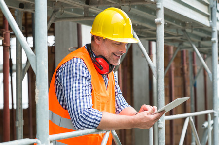 Photo for Close-up Of A Happy Male Engineer Using Digital Tablet At Construction Site - Royalty Free Image