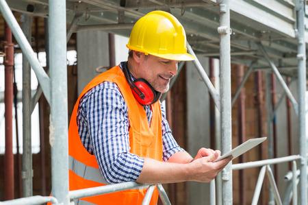 Foto de Close-up Of A Happy Male Engineer Using Digital Tablet At Construction Site - Imagen libre de derechos