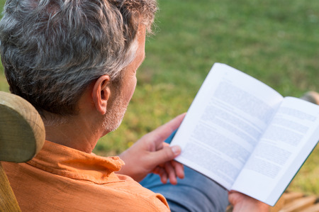 Photo pour Close-up Of Mature Man Sitting On Lounge Chair Reading Book Outdoor - image libre de droit