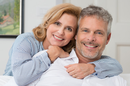 Foto de Portrait Of A Mature Couple Smiling And Embracing At Home - Imagen libre de derechos