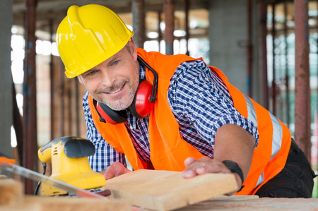 Photo for Close-up Of A Smiling Male Carpenter Looking At Wooden Plank At Construction Site - Royalty Free Image