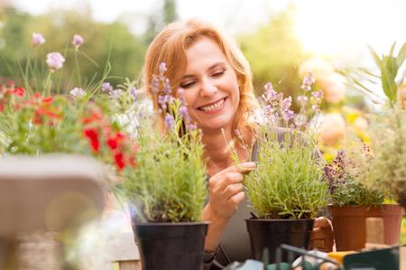Foto de Portrait Of Happy Mature Woman Arranging Plants In Garden - Imagen libre de derechos