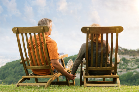 Foto de Rear View Of Mature Couple Sitting On Lounge Chair Holding Hands Conteplate the Future - Imagen libre de derechos