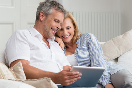 Photo pour Happy Mature Couple Sitting On Sofa With Digital Tablet - image libre de droit