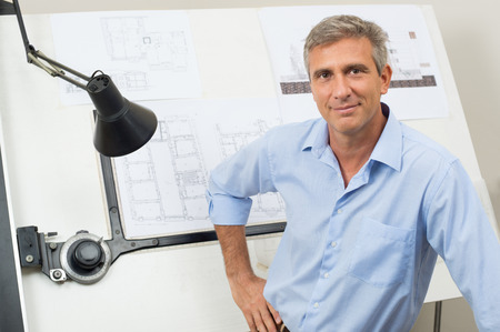 Foto de Portrait Of Male Architect With Blueprint At Office - Imagen libre de derechos