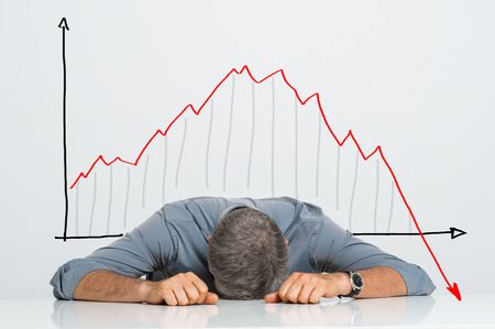 Photo pour Depressed Businessman Leaning His Head Below a Bad Stock Market Chart - image libre de droit