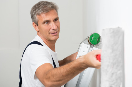 Photo for Mature Man In Uniform On Stepladder Painting Wall With Roller - Royalty Free Image