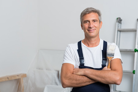 Photo for Portrait Of Smiling Painter With Arm Crossed Holding Paintbrush At Home - Royalty Free Image