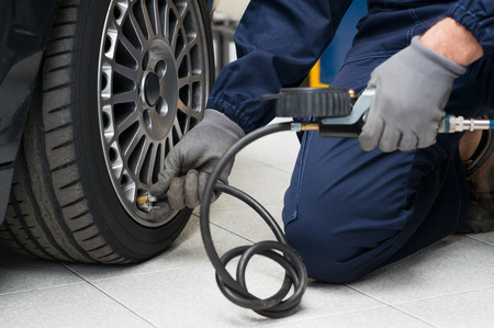 Photo for Closeup Of Mechanic At Repair Service Station Checking Tyre Pressure With Gauge - Royalty Free Image