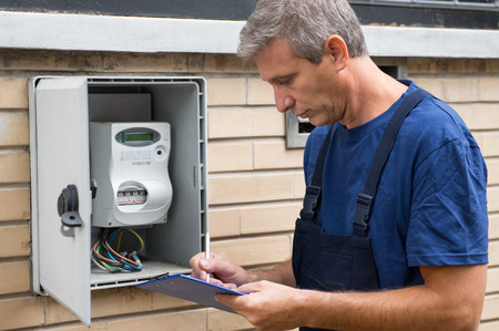 Foto de Portrait Of Electrician Worker Inspecting Electric Meter - Imagen libre de derechos