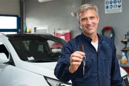 Foto de Portrait Of Mature Auto Mechanic In Garage Holding Car Key - Imagen libre de derechos