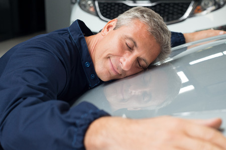 Photo for Closeup Of Mature Mechanic With Eyes Closed Lying On Car Bonnet Hugging - Royalty Free Image