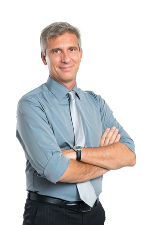 Photo pour Portrait Of Smiling Confident Mature Businessman With Arms Crossed Looking At Camera Isolated On White Background - image libre de droit