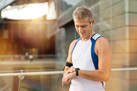 Foto de Portrait Of Happy Mature Man With Heart Rate Monitor On Wrist - Imagen libre de derechos
