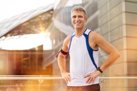 Photo pour Portrait Of Happy Mature Male Jogger With Earphone Looking At Camera Outdoor - image libre de droit