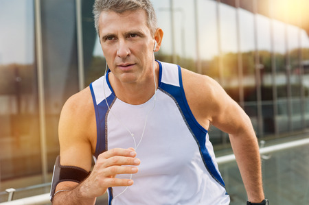 Photo pour Portrait Of A Mature Man Athlete Jogging With Earphones In A City - image libre de droit