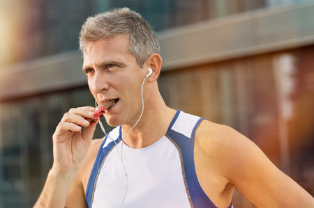 Photo for Portrait Of Fitness Mature Man Eating A Energy Bar Of Chocolate - Royalty Free Image