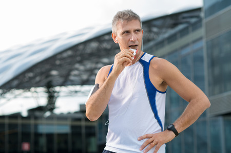 Foto per Athletic Mature Man Eating Bar Of Chocolate And Listening Music In The Urban Center - Immagine Royalty Free