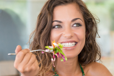 Photo pour Young Smiling Girl Eating Salad At Luch Break From Work - image libre de droit