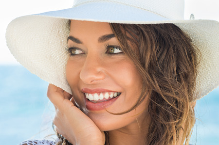 Photo pour Portrait Of Beautiful Smiling Young Woman At Beach With Sraw Hat - image libre de droit