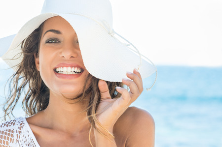 Photo pour Closeup Of Smiling Beautiful Young Woman At Beach With Straw Hat - image libre de droit