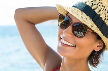Photo pour Portrait Of Smiling Young Woman Wearing Sunglasses - image libre de droit