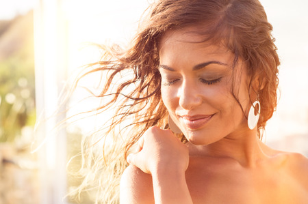 Foto de Closeup Of Smiling Young Woman With Eyes Closed At Sunset - Imagen libre de derechos