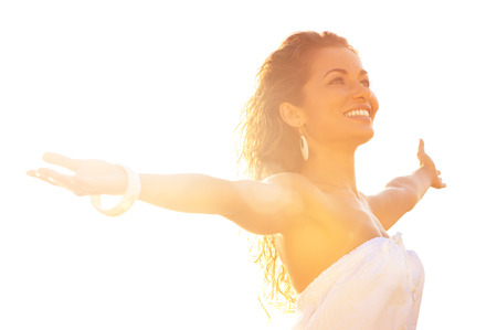 Photo for Happy Young Woman Standing With Arms Outstretched Against Sunlight In Summer - Royalty Free Image