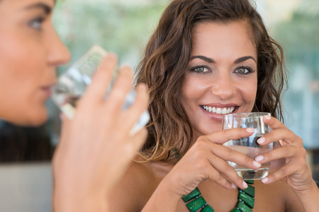 Photo for Two Female Friends Drinking Mineral Water With Glass At Bar - Royalty Free Image