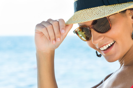 Photo pour Portrait Of Smiling Young Woman Wearing Sunglasses And Panama - image libre de droit