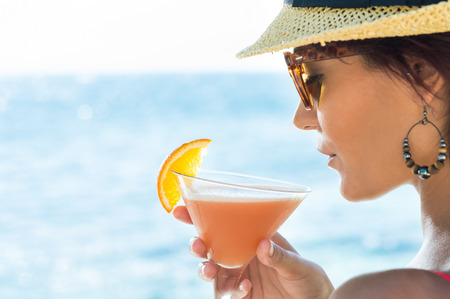 Photo pour Closeup Of Young Woman Wearing Hat And Sunglasses Holding Cocktail Glass At Seaside - image libre de droit