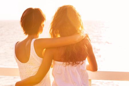 Foto de Rear View Of Two Young Women Looking At Sea At Sunset - Imagen libre de derechos