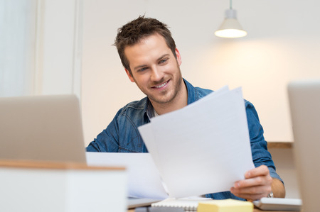 Photo pour Happy young businessman reading paperwork at desk in office - image libre de droit