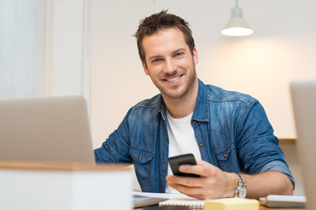 Foto de Smiling young casual business man with mobile phone in the hand - Imagen libre de derechos