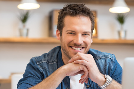 Photo for Closeup of smiling young businessman looking at camera in office - Royalty Free Image