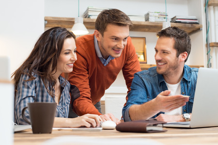 Foto de Business people smiling together while looking at laptop in office - Imagen libre de derechos