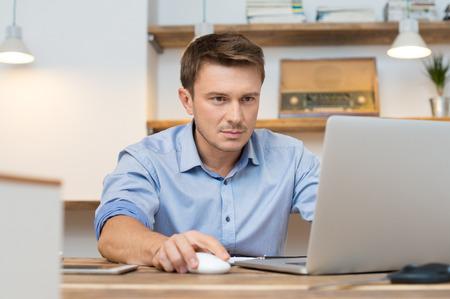 Foto de Portrait of young businessman using laptop in office - Imagen libre de derechos