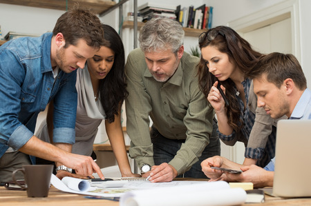 Photo for Architects working and discussing on blueprints at office - Royalty Free Image