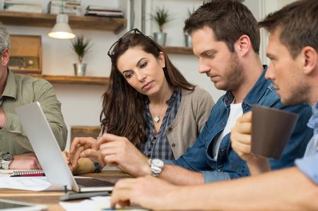 Foto de Business people looking at laptop and working together in office - Imagen libre de derechos
