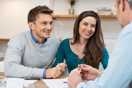 Foto de Young couple meeting financial advisor for investment - Imagen libre de derechos