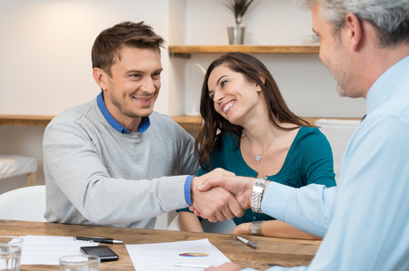 Photo pour Happy young couple shaking hands for a financial agreement - image libre de droit