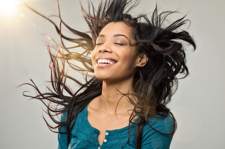 Photo pour Closeup of smiling young woman blowing her hair in the wind - image libre de droit