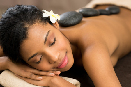 Photo pour Beautiful young woman with eyes closed receiving hot stone massage at salon spa - image libre de droit