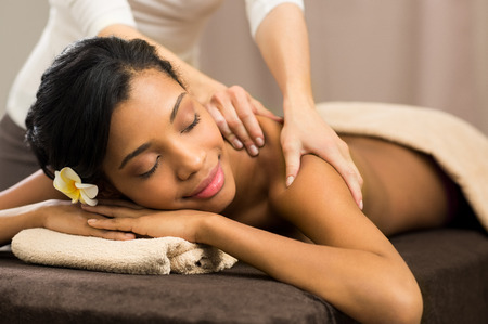 Closeup of happy african woman receiving back massage at salon spa