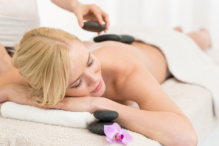 Photo for Beautiful young woman receiving hot stone massage at salon spa - Royalty Free Image