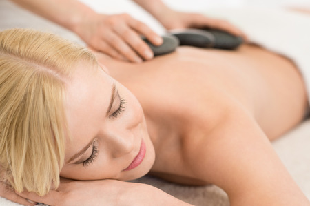 Photo for Beautiful young woman receiving hot stone massage - Royalty Free Image