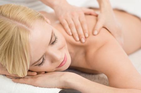 Photo pour Closeup of happy young woman receiving massage at salon spa - image libre de droit